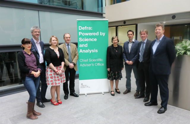 The Systems Research Programme fellows and CSA Ian Boyd standing in a row in front of a banner which reads 'Defra: Powered by Science and Analysis, Chief Scientific Adviser's Office'.