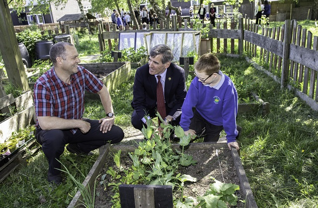Image of Minister David Rutley, a teacher and a pupil sat next to a raised bed of plants