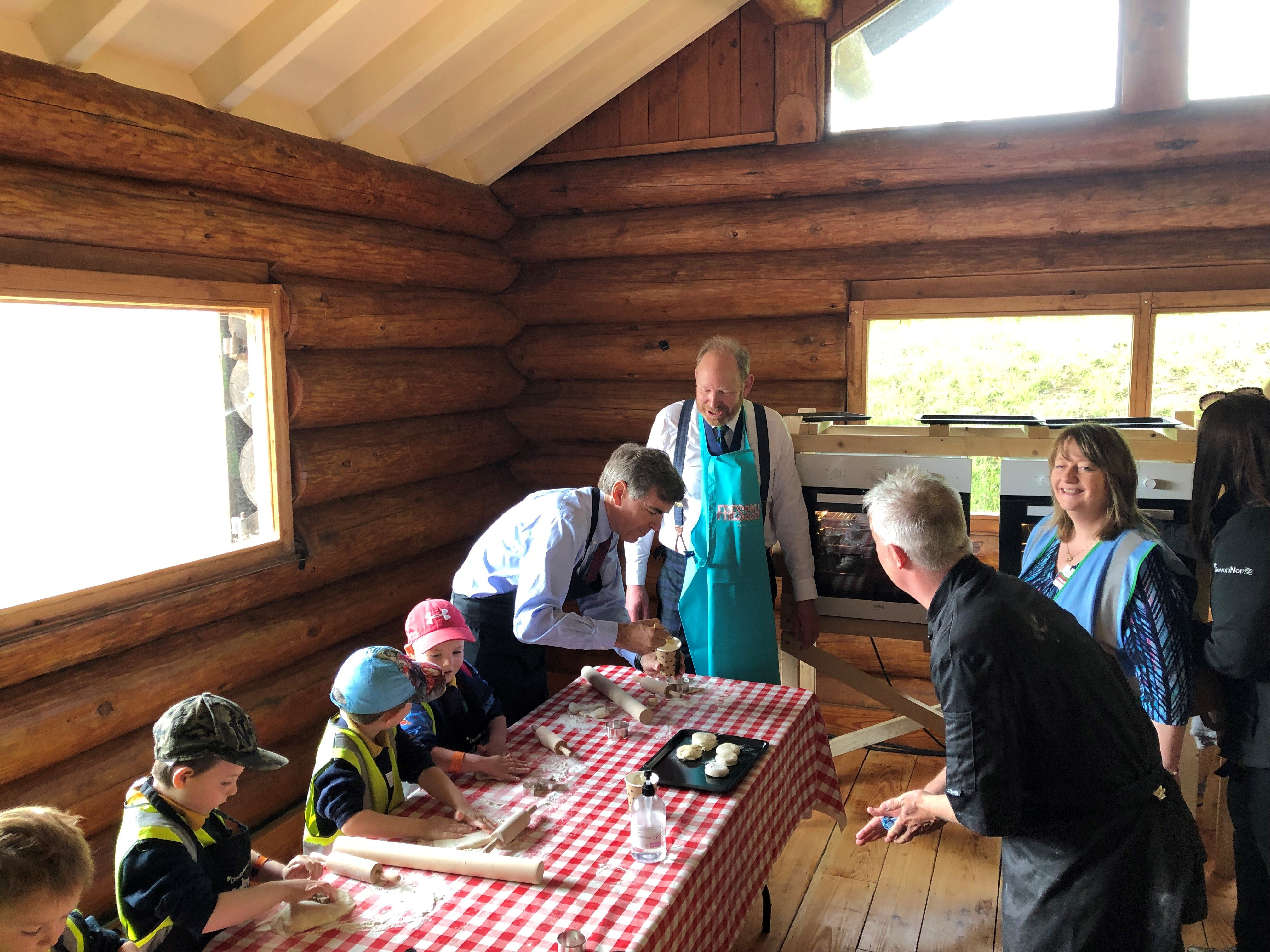 image of minister Rutley and sit Harry Studholme making scones with school children.