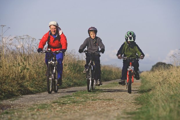 A man and two children riding bikes with helmets on down a path.