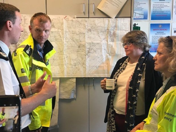 An image of Minister Coffey and Environment Agency officer's in front of a map of Lincolnshire