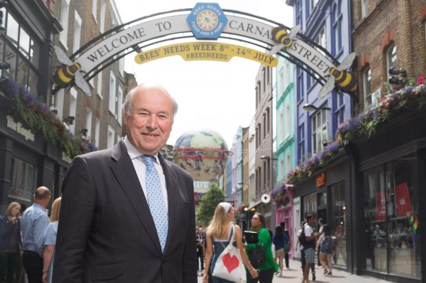Lord Gardiner, Defra Biosecurity Minister, stands under the famous Carnaby Street which has been rebranded for Bees' Needs Week with images of bees.