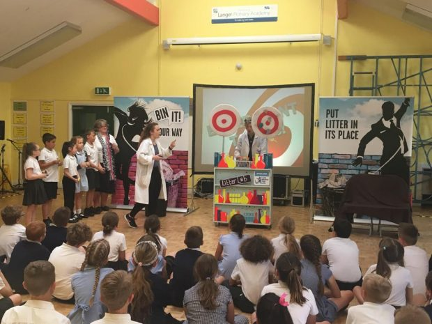 Image of school children and Minister Therese Coffey standing up in front of an audience of children at the Bin It Roadshow. The sign on the wall says 'bin it your way' and 'put litter in its place'
