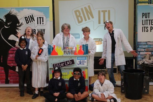 Image of Minister Therese Coffey standing with children and an actor behind a sign that says 'Litter Lab' and 'Bin It!'