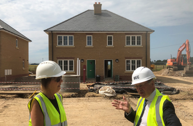 English Rural's Senior Regional Development Director Alison Thompson and Lord Gardiner stand outside a housing construction site in Throwley Kent