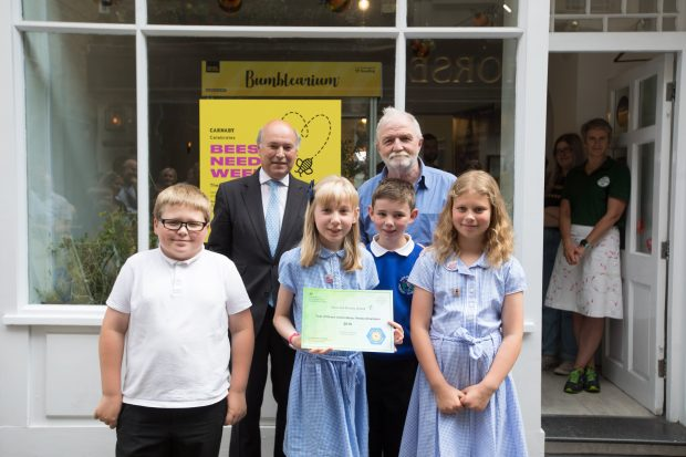 Lord Gardiner, George McGavin and pupils from the Heron Hill primary school in Kendal stand in front of the 'Hive' on 3 Newburgh Street. The pupils are holding their Bees' Needs School Award certificate which recognises their efforts to help pollinating insects.