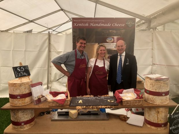 Lord Gardiner with two people at a stall selling cheese