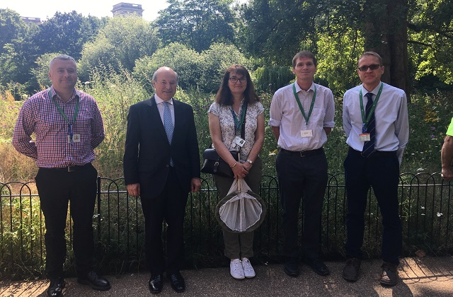Lord Gardiner stands in front of wildflower meadow in St James's Park with Robert Dowling, Assistant Park Manager, Claudia Watts, Greenspace Information for Greater London, Peter Lawrence, Head of Ecology and Tom Jarvis, Director of Parks.