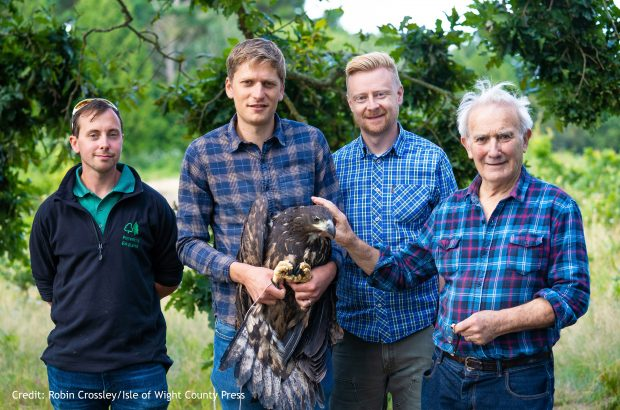 Four people stood holding one of the eagles