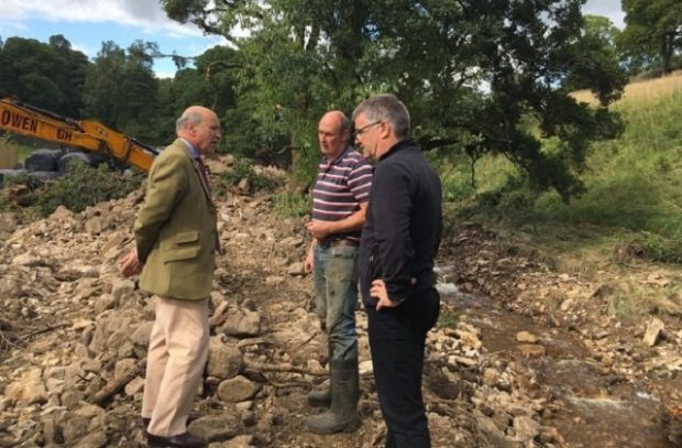 Lord Gardiner speaking with two farmers standing next to a stream in the Yorkshire Dales