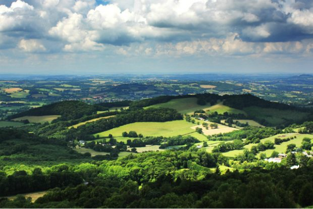 A wide-angle image of the Malvern Hills landscape in the sunlight with the clouds and sky above