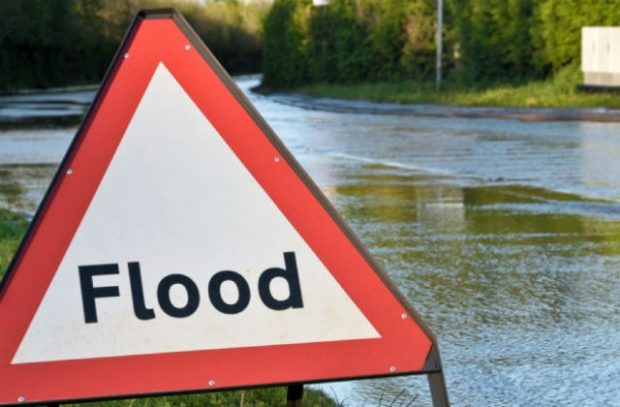 Image of a flood sign against a flooded backdrop.