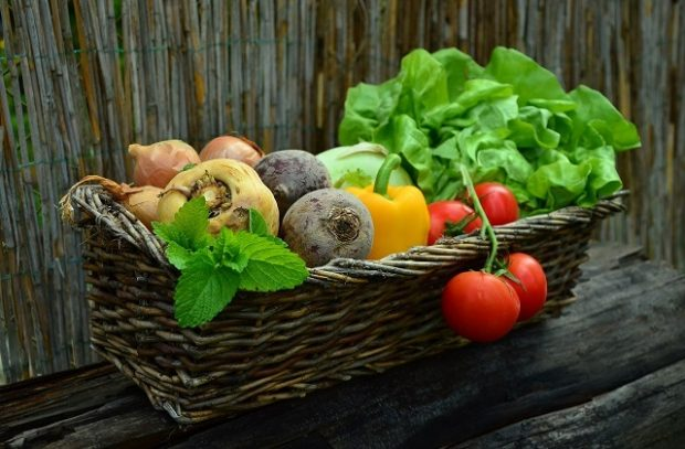 A brown wicker basket of vegetables including lettuce, tomatoes and peppers on a brown background.