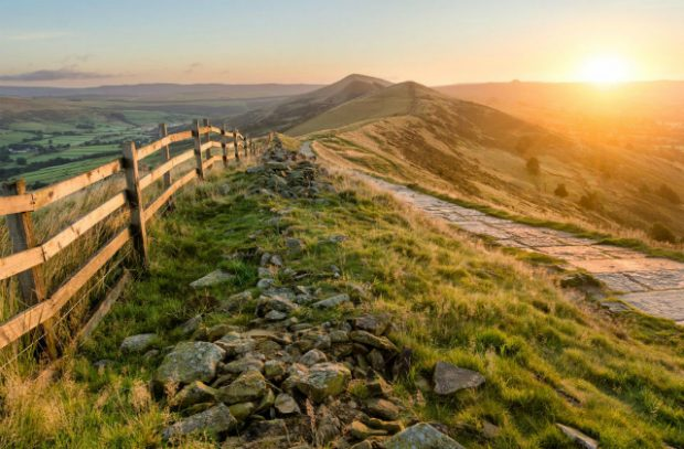 A sunset over a range of hills, with a footpath and fence running through it