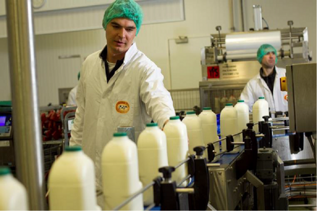 Two men at a milk processing unit where bottles of milk sit on a production line