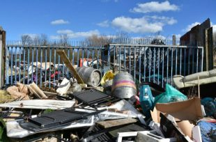 A pile of mixed waste, including chairs, roof insulation and beer barrels, that has been fly-tipped