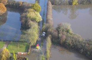 Arial shot of van driving through farmland flooded in November 2019