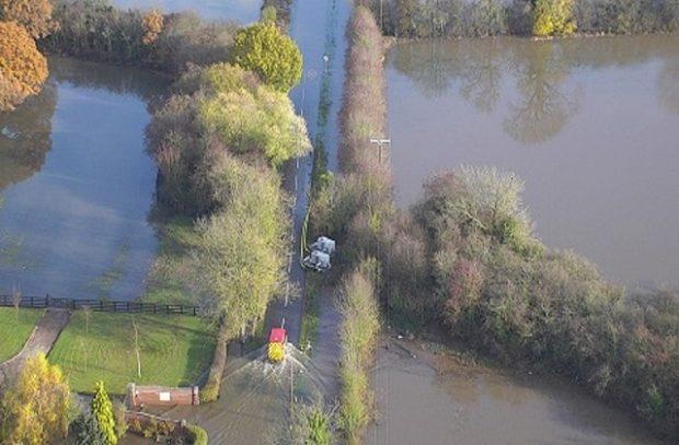 Arial shot of van driving through farmland flooded in November 2019