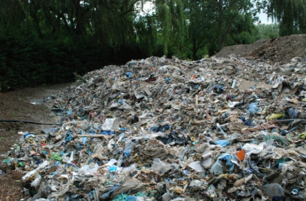A picture showing tonnes of mixed waste that has been dumped on private rural land