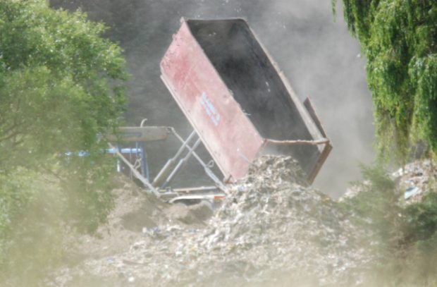 A photo of a tipper lorry dumping waste illegally on private land