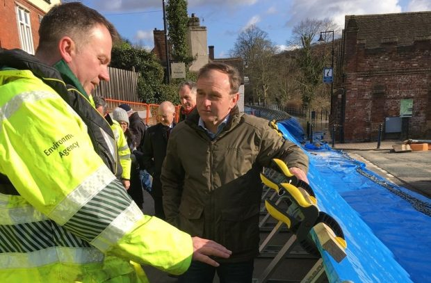 environment agency staff member and george eustice inspect flood defences