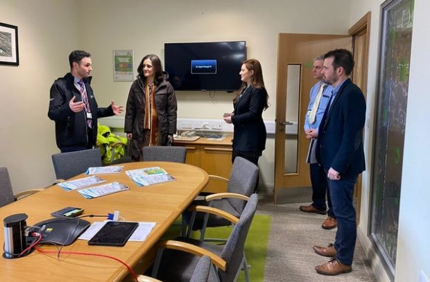 Environment Secretary Theresa Villiers in a room with four Environment Agency staff members standing in front of a table with paper documents on