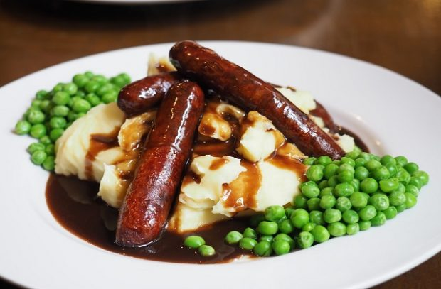 Sausages, peas and mashed potatoes with gravy on a plate