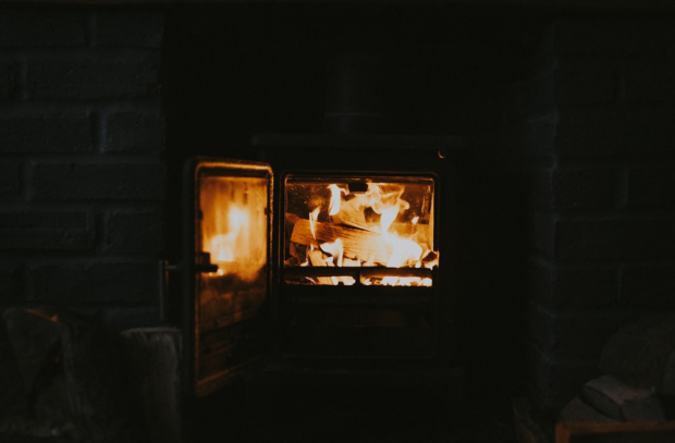 several wooden logs burning in a stove inside a brick fireplace