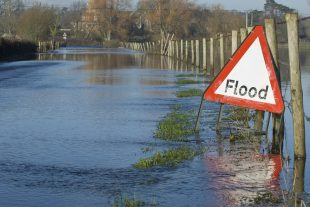 A flood warning sign, on a closed country road next to water logged fields in the Avon Valley, Hampshire, England. Flooded after an extreme amount of rainfall at the start of 2014