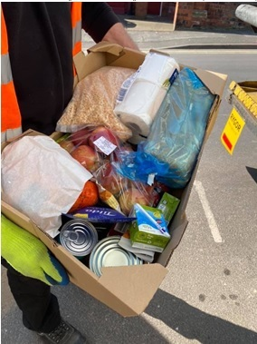 A person holds a food box containing items such as tinned goods, rice and fruit