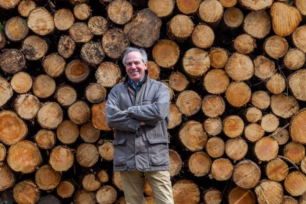 Image of Sir William Worsley standing in front of log pile