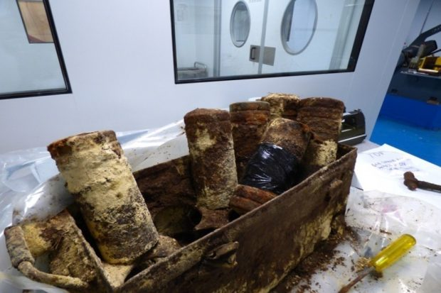 A rusted and dirty box containing numerous mustard gas canisters.
