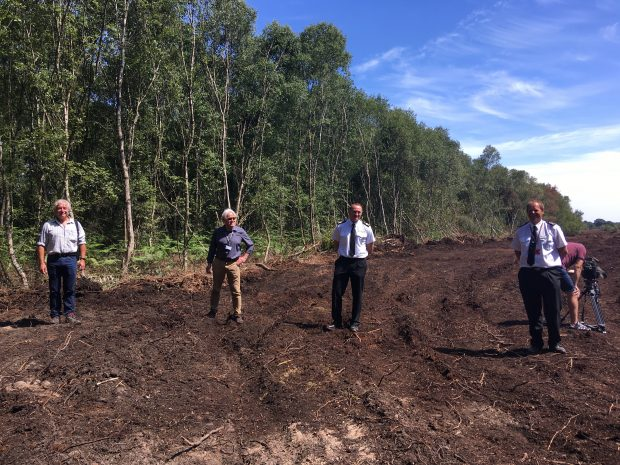 Tony Juniper, Damian Allen from Doncaster Council, and two men from South Yorkshire Fire and Rescue Service stand in a field at the Hatfield Moor site