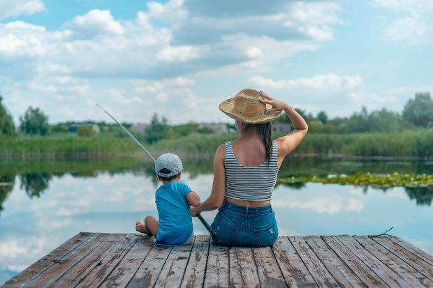 A woman and young boy sat fishing on a dock, facing away from the camera.