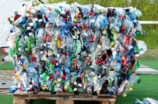 A large consignment of flattened plastic bottles, crused into a cube shape