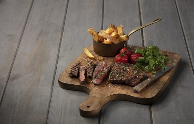 An image of a ribeye steak with vegetables on a wooden board