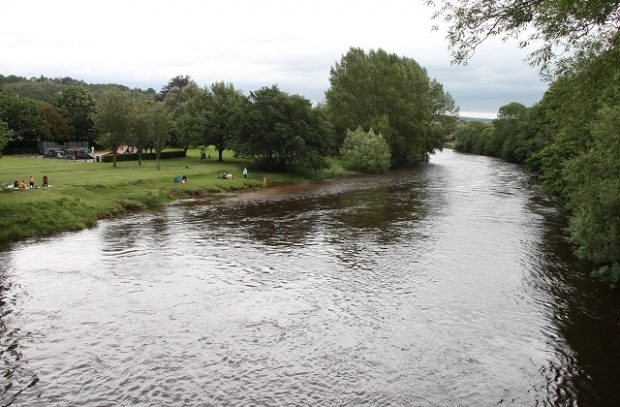 People standing on the bank of the River Wharfe near Ilkely