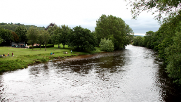 People standing on the green banks of the River Wharfe near Ilkley