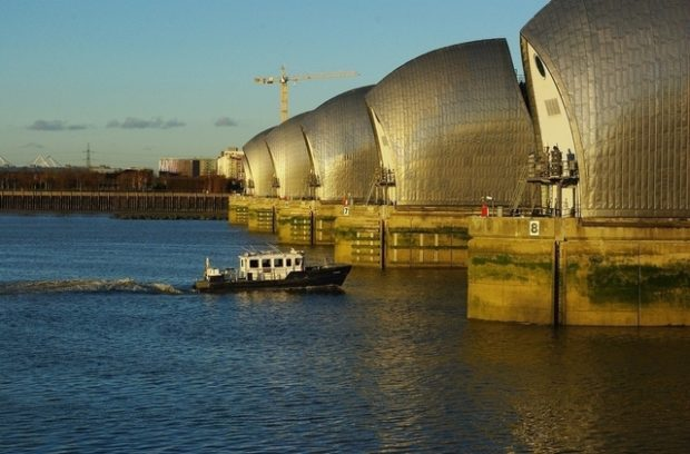 Motorised boat sailing into the Thames Barrier on a sunny day