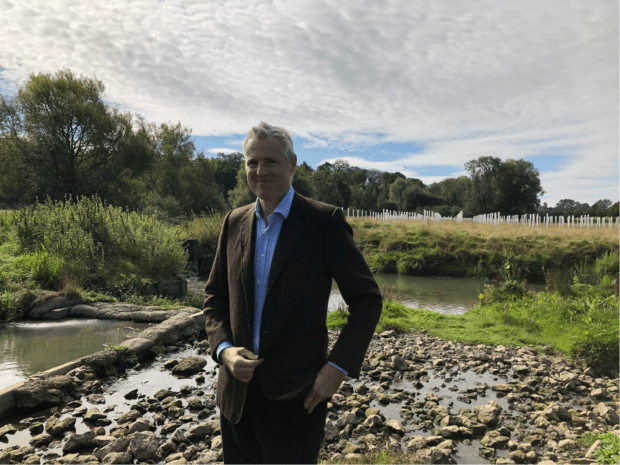 Image of Lord Goldsmith in front of a riverbank with trees in background.